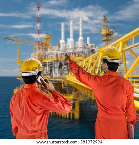 Oil workers in orange uniform and helmet with rig background  - stock photo