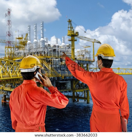 Oil workers in orange uniform and helmet with rig background