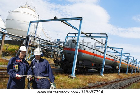 oil workers with industrial train carrying fuel and oil as cargo, inside refinery actions. - stock photo