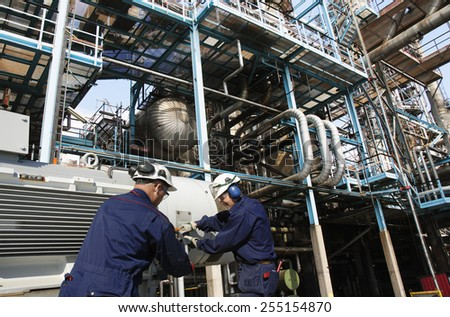 oil workers with machinery pumps inside large petroleum refinery - stock photo