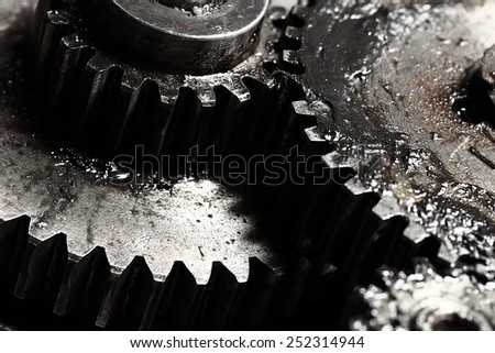 Oiled gears as small parts of large mechanism - stock photo