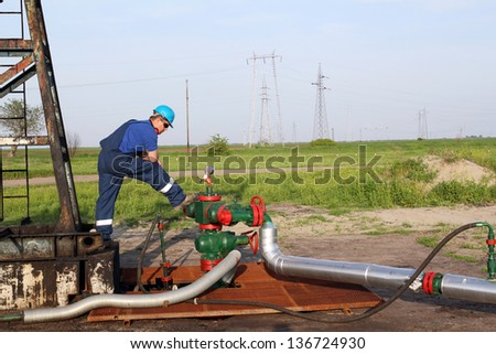 oilfield with worker and pipeline - stock photo