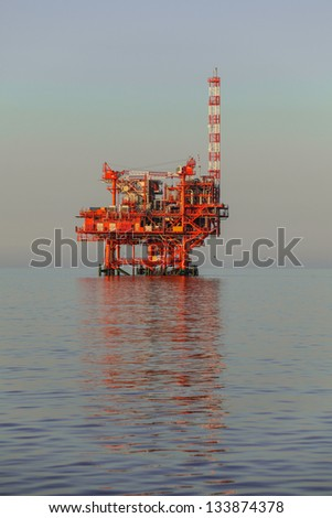 oilrig lit by the rising sun - stock photo
