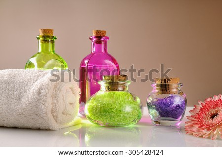 Oils and bath salts on white glass table. Decorated with flower and towel with brown gradient background.