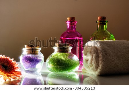 Oils and bath salts on white glass table with dimly light. Decorated with flower and towel with brown gradient background.