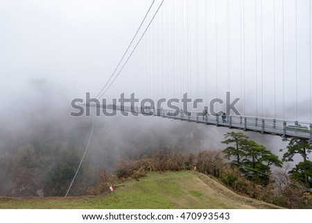 "Oita,Japan - November 25, 2015:  Kokonoe ""Yume"" Grand Suspension Bridge in foggy day, It is 173m tall and 390m long."