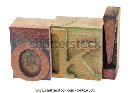 OK in vintage wooden letterpress type blocks, stained by color ink, isolated on white - stock photo