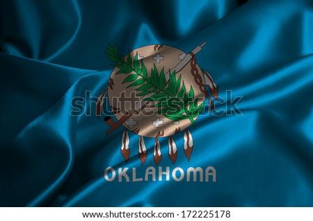 Oklahoma flag on satin texture. - stock photo