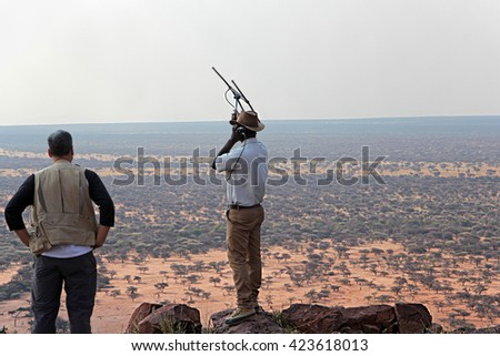 OKONJIMA, NAMIBIA - SEPTEMBER 11, 2015: Safari guide waves VHF antenna from hilltop to locate wild animals wearing tracking collars under the watchful eye of a tourist photographer.