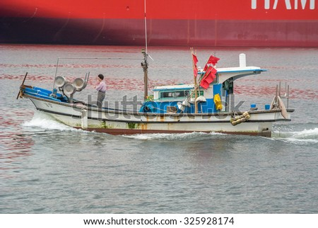 OKPO, SOUTH KOREA-SEPTEMBER 5 2015: A small fisihing boat sailing past a large ship under construction at the DSME shipyard.