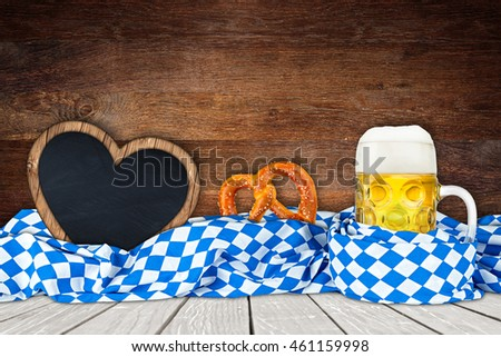 Oktoberfest background with beer mug bavarian flag and empty heart shaped blackboard