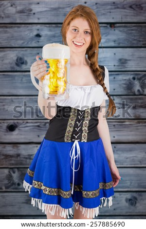 Oktoberfest girl smiling at camera holding beer against wooden background in blue - stock photo