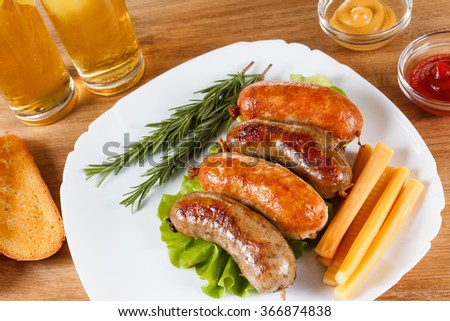 Oktoberfest traditional menu, beer and roast beef or chicken sausage  with ketchup, mustard and rosemary. Wooden background - stock photo