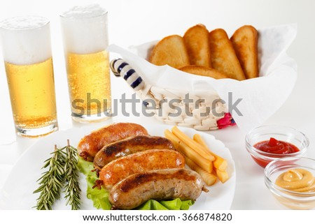 Oktoberfest traditional menu, roast beef or chicken sausage on a plate with ketchup, mustard and rosemary. White background - stock photo