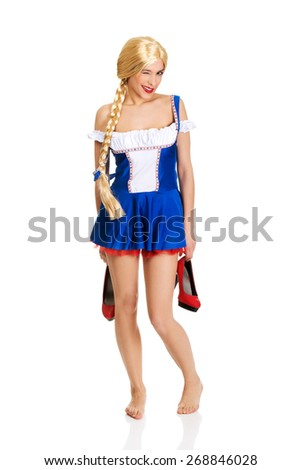 Oktoberfest woman in Bavarian dress holding her shoes. - stock photo