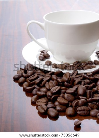OLColor photo of coffee beans and a white cup