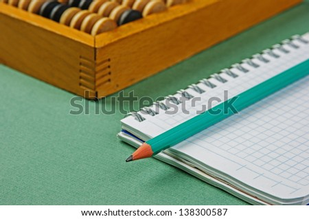 old abacus and notebook on the green background