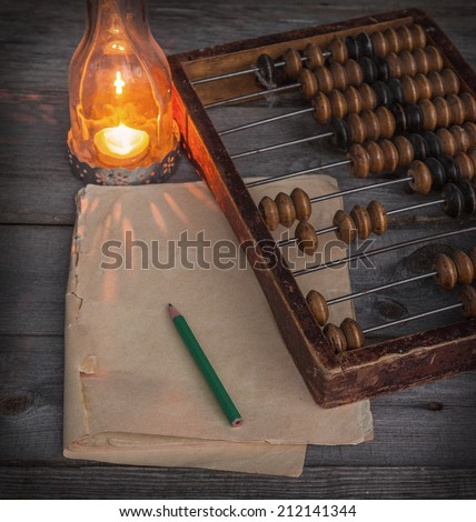 Old abacus, the paper with a pencil next to a  lamp on a wooden table - stock photo