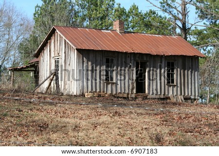 Old abandon house in a field with tin roof and old wood siding - stock photo