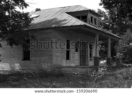 Old abandon house in south-central Kentucky weathered wood texture eerie serene rural country farm haunted Halloween scary grass weeds broken decay monochrome black white
