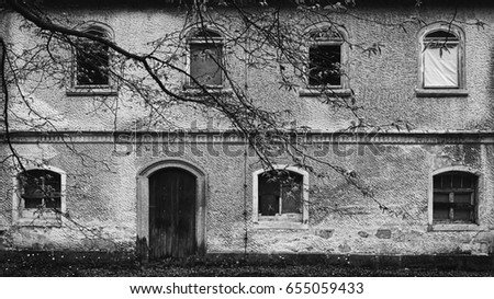old abandoned and decayed ddr castle front with branches in black and white