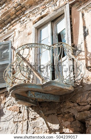 Old abandoned balcony and window on stone made house.Syros island,Greece