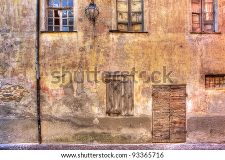 Old abandoned brick house with vintage wooden door and window in town of Serralunga D'Alba, Northern Italy.
