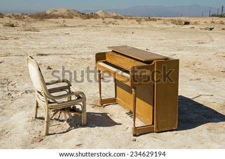 old abandoned broken piano and chair near the Salton Sea - stock photo