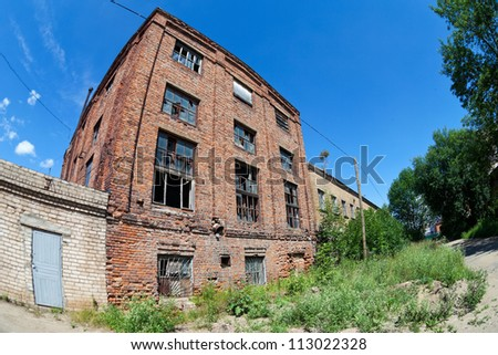 Old abandoned building against blue sky in summer day