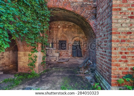 Old abandoned building with an arch with ivy.