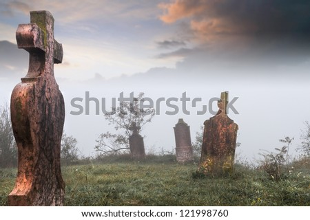 Old, abandoned cemetery  on a cold, foggy morning - stock photo