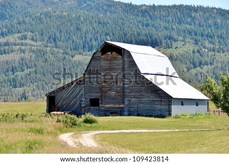old abandoned farm building in mountains - stock photo