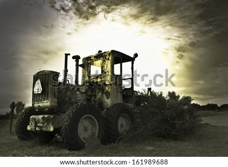 Old abandoned farm grader machine in a field in Florida - stock photo