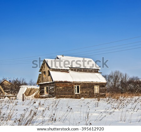 Old abandoned farm house in a frosty winter  - stock photo
