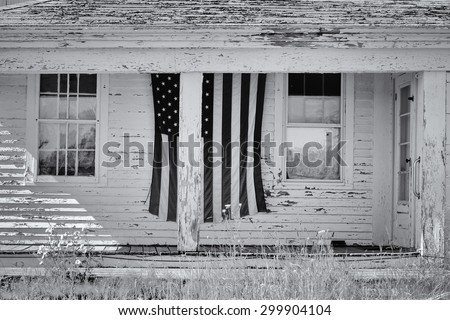 Old abandoned farm house with a large worn porch veranda and a large american flag sits empty with it's peeling wood and paint  - stock photo
