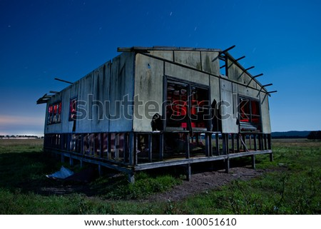 Old abandoned farmhouse at night - stock photo
