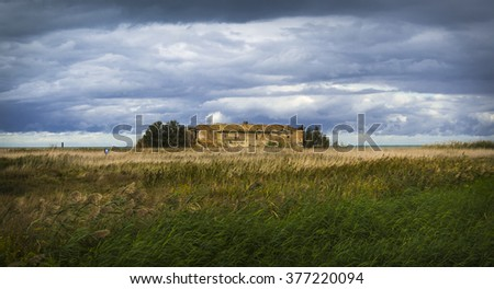 Old abandoned farmhouse near the sea, in a meadow, under a cloudy sky  - stock photo