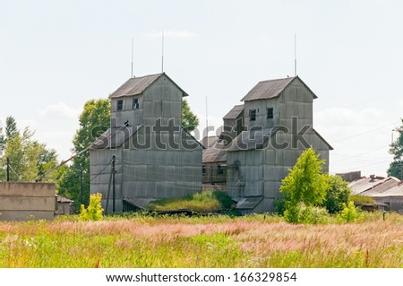 Old abandoned grain elevator against blue sky background.  - stock photo
