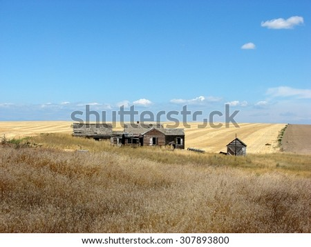 old abandoned homestead buildings on the prairie - stock photo