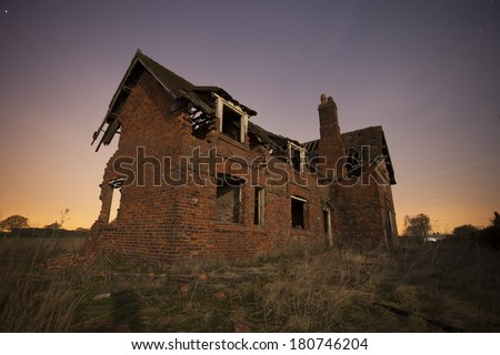old abandoned house at night with star trails - stock photo