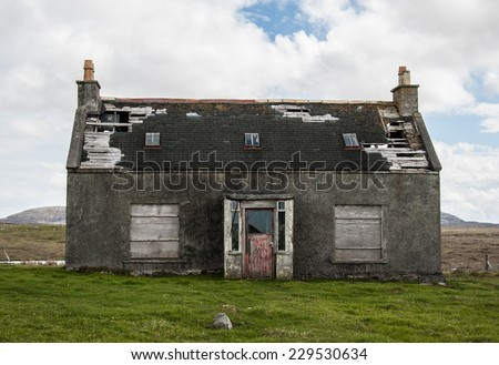 Old abandoned house in the countryside with broken roof and windows - stock photo