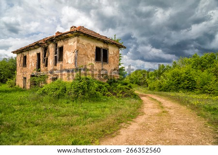 Old abandoned house in the storm. - stock photo