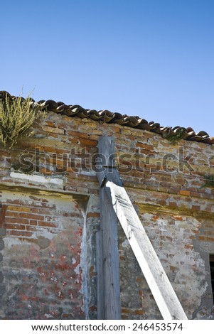 Old abandoned house with a brick wall supported by wooden beams - stock photo