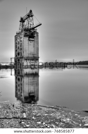 Old, abandoned industrial building with reflective water in the foreground during night time, Black and white image