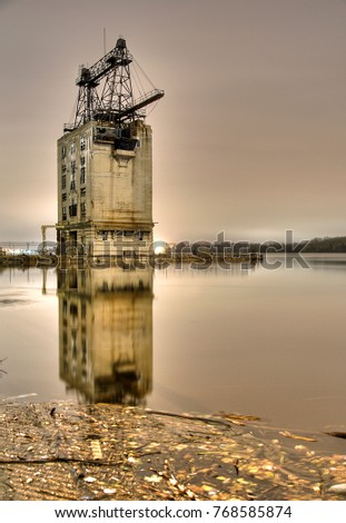 Old, abandoned industrial building with reflective water in the foreground during night time with beautiful warm toned colors