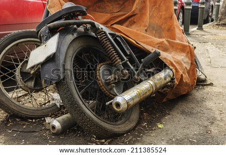 Old abandoned motorcycle with rusty components .