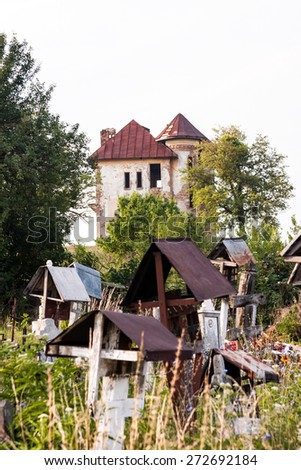 Old, abandoned, ruined house in the field with cemetery - stock photo