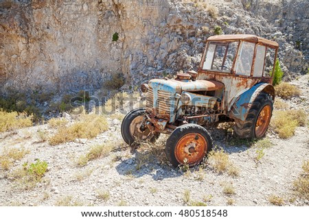 Old abandoned rusted tractor stands on dry summer meadow