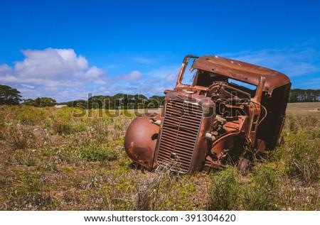 Old abandoned rusty car wreck in rural Australian farm field - stock photo