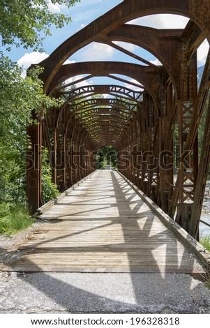 Old abandoned rusty railroad bridge used for bike lane for passing Sava Dolinka - stock photo